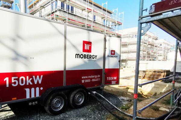 Mobile Heizzentrale von Mobergy vor der Baustelle eines Hauses.