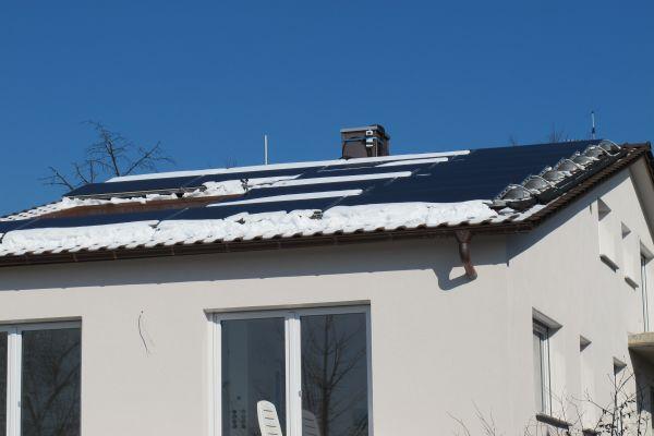 Ein Haus mit PV-Kollektoren auf dem Dach.