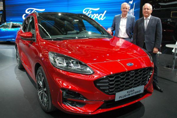 Zwei Männer stehen neben einem roten Auto.
