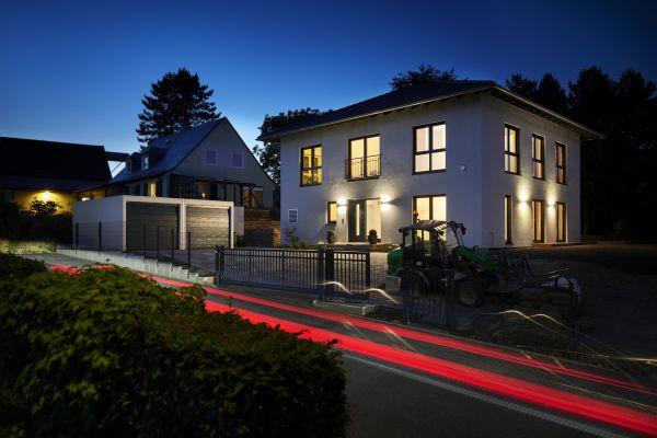 Drei beleuchtete Häuser bei Nacht.