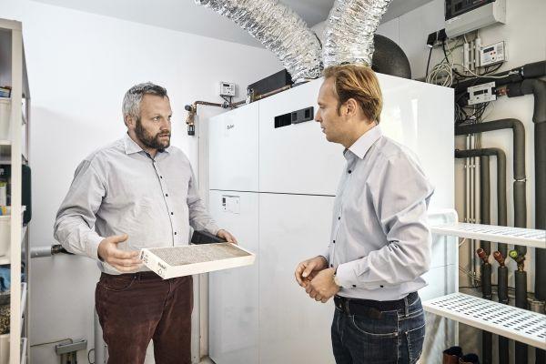 Für Sebastian Pönsgen (li.) vom Fachhandwerksunternehmen Priogo ist das einfache Handling der Wärmepumpe mit integrierter Wohnraumlüftung ein wichtiges Verkaufsargument im Gespräch mit dem Endkunden. Bis hin zum einmal jährlich obligatorischen Luftfilterwechsel, der im wahrsten Sinne des Wortes  mit einem Handgriff erledigt ist.