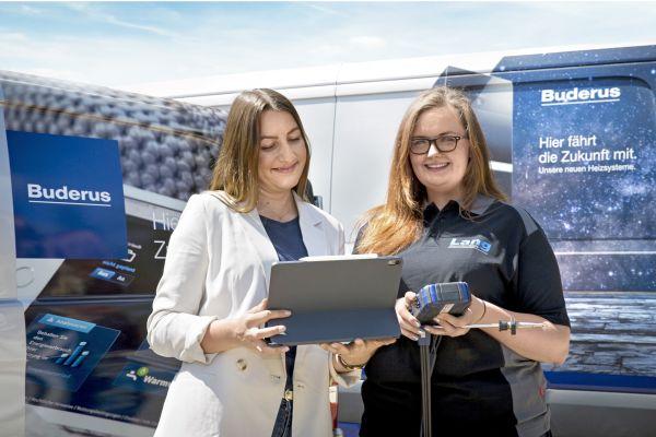 Zwei Frauen stehen mit einem Tablet vor einem Transporter.