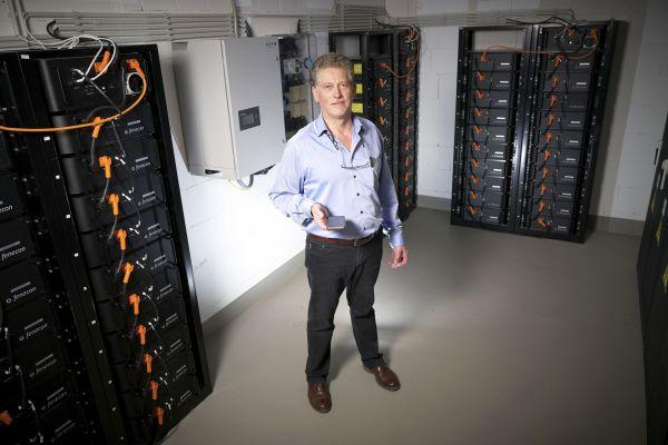 Geschäftsführer Andries Broekhuijsen im Keller mit seinen Stromspeicher-Einheiten: Per App kann er die aktuellen Speicherstände einsehen. 400 kWh Gesamtspeicherkapazität stehen zur Verfügung, um den aus den PV-Anlagen gewonnenen Strom zu speichern.