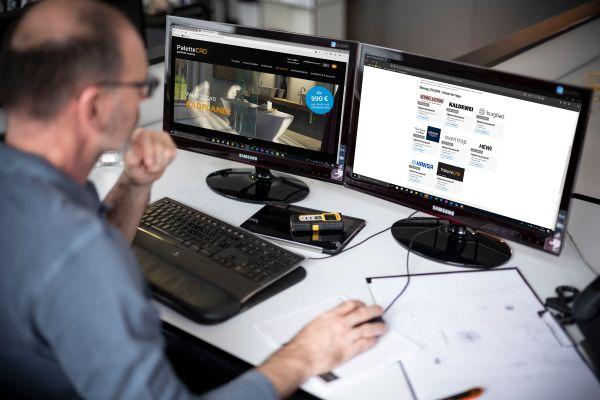 Ein Mann sitzt an einem Schreibtisch vor zwei Computer-Bildschirmen.