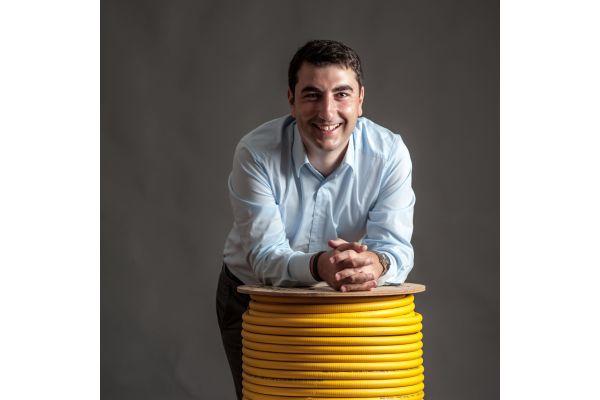 Ein Mann lehnt sich auf eine Rolle mit gelbem Edelstahl-Wellrohr.