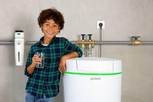 Das Bild zeigt ein Kind vor einer Wasseraufbereitungsanlage von Grünbeck.