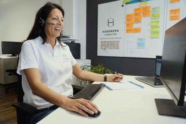 Eine Frau sitzt vor einem Computer-Bildschirm.