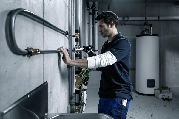 Das Bild zeigt einen Installateur an einer Trinkwasserleitung.