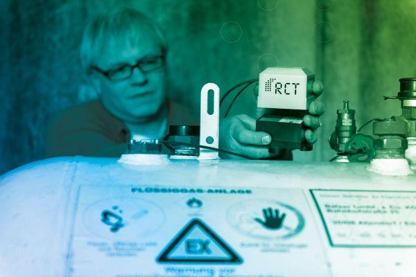 Ein Mann bringt ein Füllstandsmessgerät auf einem Tank an.