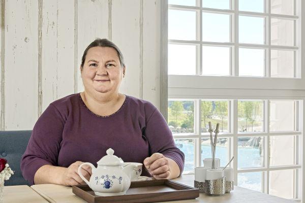 Eine Frau sitzt an einem Tisch, vor ihr steht eine Teekanne auf einem Tablett.