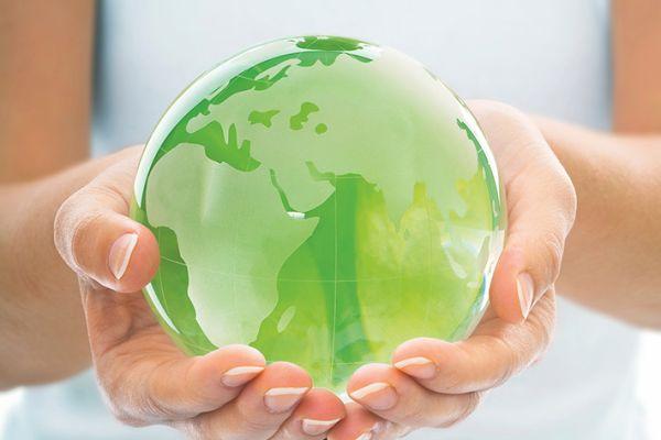 Das Bild zeigt Hände, die eine grüne Weltkugel tragen.