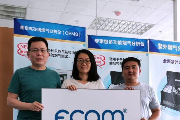 Drei Menschen stehen nebeneinander und halten ein Schild mit dem ecom-Logo.