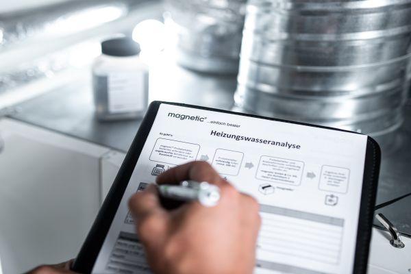 Jemand füllt auf einem Klemmbrett ein Formular zur Heizungswasser-Analyse aus.
