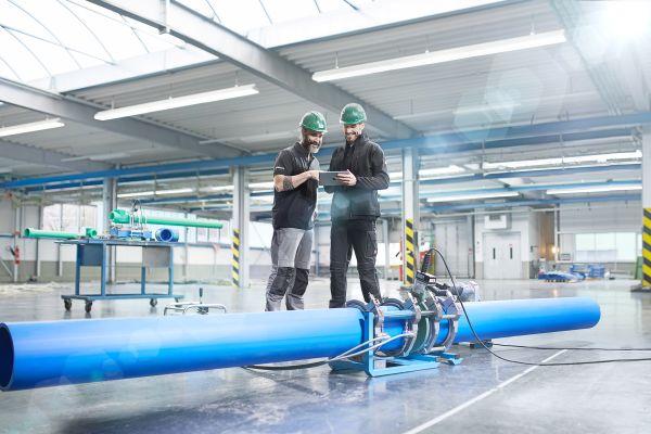 Zwei Männer stehen mit einem Tablet neben einem blauen Rohr.
