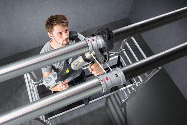 Ein Handwerker installiert ein Rohrleitungssystem.