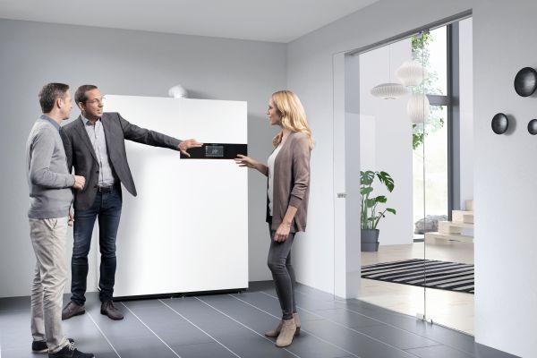 Zwei Männer und eine Frau stehen neben einen Brennstoffzellenheizgerät.