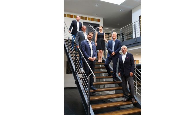Fünf Männer und eine Frau stehen auf Treppenstufen.