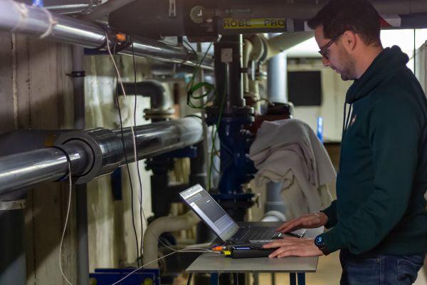 Ein Mann arbeitet in einem Heiztechnikraum an einem Laptop.