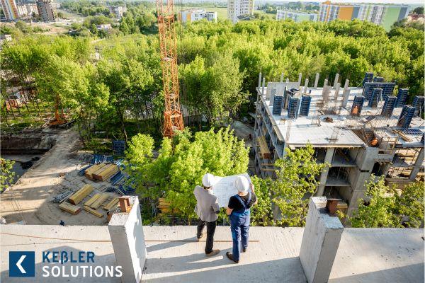 Zwei Männer stehen mit einem Bauplan auf dem Rohbau eines Gebäudes.