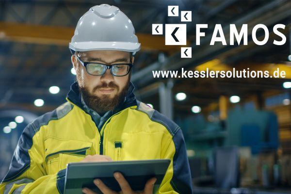 Ein Mann steht mit einem Tablet auf einer Baustelle.