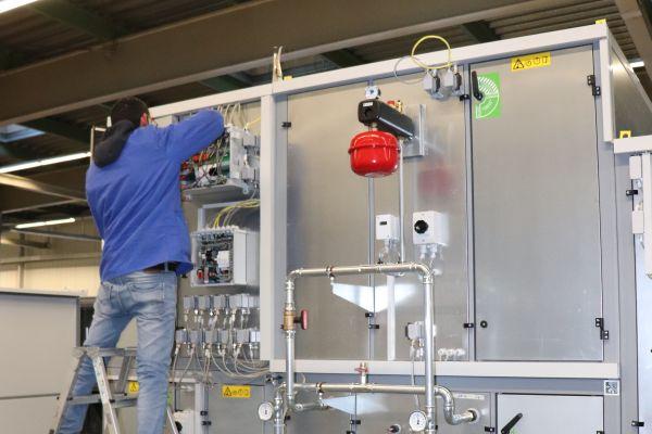 Ein Mann arbeitet an einer RLT-Anlage.