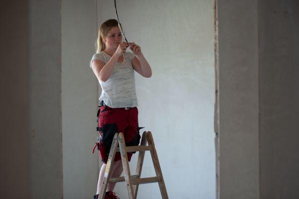Eine Handwerkerin steht auf einer Leiter.