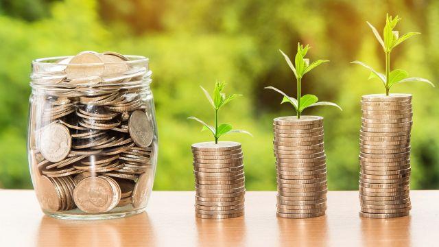 Drei Türmchen aus Münzen, aus denen Pflänzchen wachsen, daneben ein Glas voll Münzen.