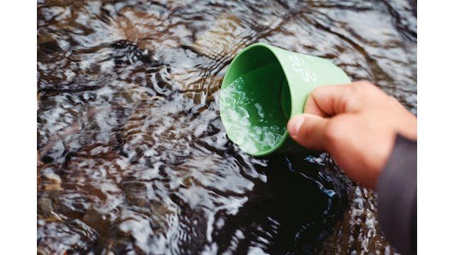 Das Bild zeigt eine Hand, die eine Tasse in ein Gewässer hält.