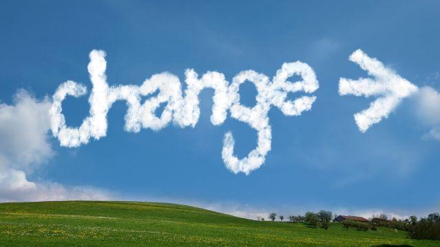Das Wort Change wie aus Wolken gemalt auf einem Himmel über einer grünen Wiese.