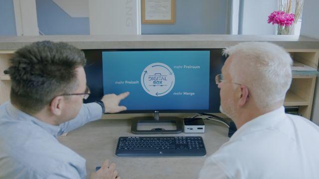 Das Bild zeigt zwei Männer am PC.