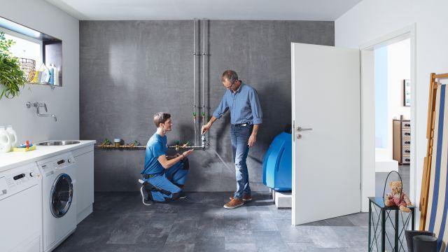 Zwei Männer neben einer Rohrleitung in einem Kellerraum.