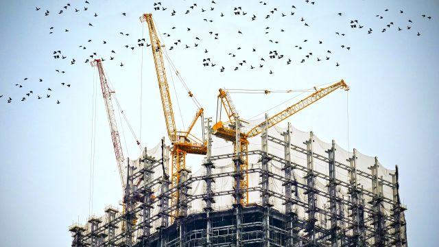 Eine Baustelle für ein größeres Gebäude mit Gerüsten und drei Kränen.