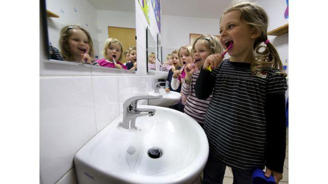 Das Bild zeigt Kinder beim Zähneputzen.