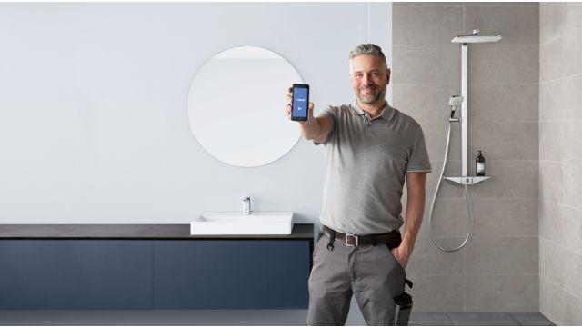 Das Bild zeigt einen Mann mit einem Handy in der Hand.