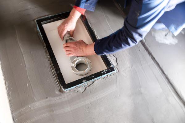 """Bevor die Duschwanne aufgesetzt wird, muss noch der Ablauf hergestellt werden, in diesem Fall die selbstreinigende Ablaufgarnitur """"BetteSolid""""."""