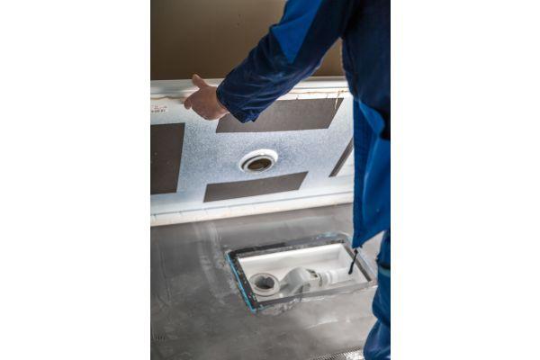 """Der """"Minimum-Wannenträger"""" wurde bereits ab Werk mit der Duschwanne vorkonfektioniert. Der Installateur muss nur noch den Kleber aufbringen und die Duschwanne auf den Estrich kleben."""