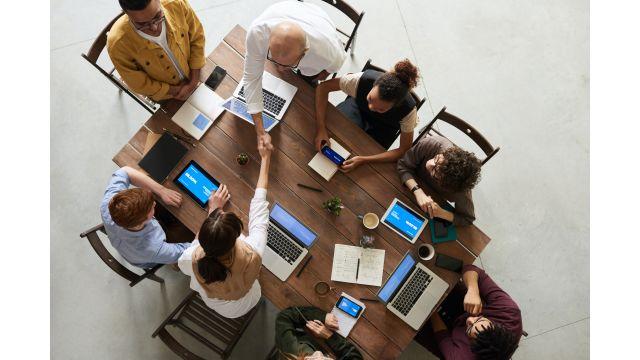 Das Bild zeigt Geschäftsleute an einem Tisch.
