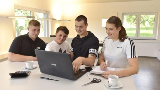 Vier Teenager sitzen um einem Laptop.