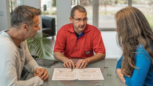 Zwei Männer und eine Frau sitzen an einem Tisch, in der Mitte liegt ein Blatt Papier.