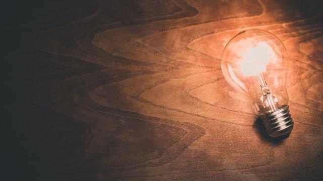 Eine brennende Glühbirne vor braunem Hintergrund.