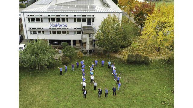 Menschen bilden eine 10 auf einem Rasen.