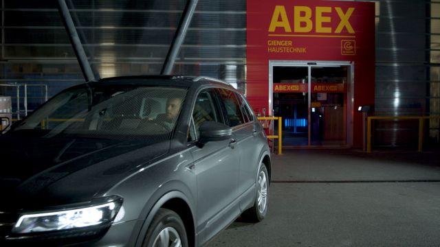 Das Bild zeigt einen Mann im Auto, der vor verschlossenen Türen eines ABEX-Einkaufsmarktes steht.