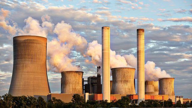 Das Bild zeigt rauchende Schornsteine eines Kraftwerks.