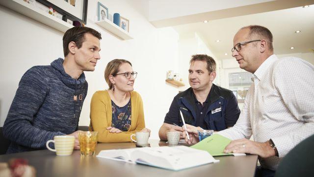 Wim und Tanja Kaiser, SHK-Fachhandwerker Christoph Freissler und Vaillant-Fachberater Andreas Hoberg im Gespräch an einem Tisch.
