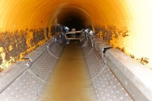 """Die Tauscherstrecke im Kanal hat eine Länge von 15 m und besteht aus einzelnen Edelstahl-Segmenten. Diese wurden über den Kanalschacht in die Abwassertrasse, Nennweite 1,20 m, eingebracht, zusammengesteckt und auf der Sohle verlegt. Die kalkulierte Leistung bei einer mittleren Abwassertemperatur von 14 °C beträgt 40 kW. Die Wärmequelle """"Kanalisation"""" bedient eine zweistufige Wasser/Wasser-Wärmepumpe."""