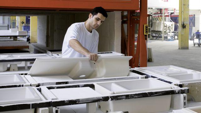 Das Foto zeigt einen Mitarbeiter mit Keramikspülen und -becken.