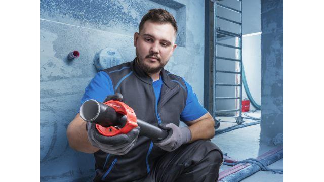 Das Bild zeigt einen Handwerker auf der Baustelle, der den Rohrabschneider um ein Kunststoffrohr hält.