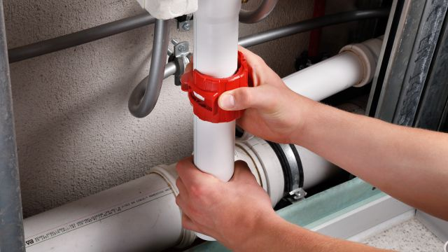 Das Bild zeigt zwei Hände, eine Hand umfasst ein senkrecht verlegtes Kunststoffrohr, die andere Hand den um dieses Rohr gelegten Rohrabschneider.