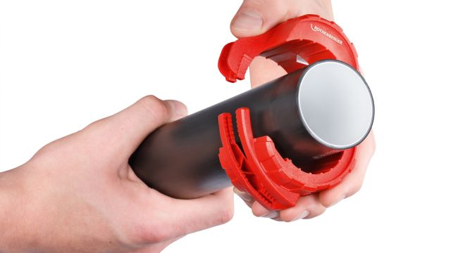 Das Bild zeigt eine Hand, die ein Kunststoffrohr hält, während die andere Hand den Rohrabschneider um dieses Rohr legt.