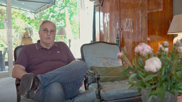 Ein Mann sitzt auf einem Sessel in einem Wohnzimmer.